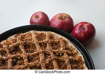 Freshly baked apple pie with apples in the background