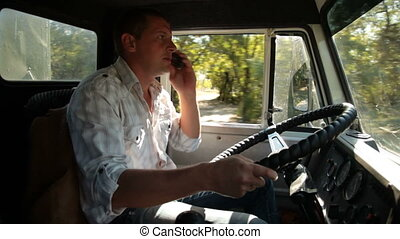 Truck Driver in Cab - Driver Using Mobile Phone in Cab of...