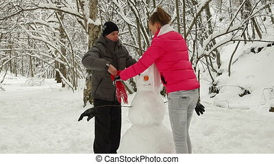 Building Snowman  In Winter Forest