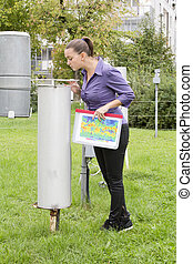 Young woman meteorologist inspecting meteorological...