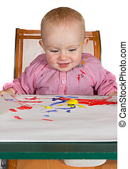 Happy baby girl playing with paint