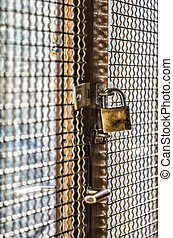 Locked down - Padlock hanging in barred window