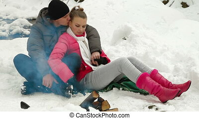 Warming Up by Bonfire in Winter - Teenage Couple Enjoying...