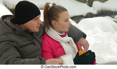 Warming Up by Bonfire in Winter - Young couple sitting by...
