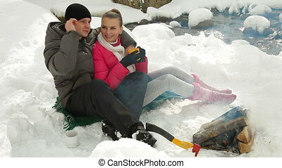 Couple Warming Up by Bonfire - Young couple sitting by...