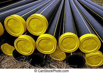 Black plastic pipes with yellow caps and stored for assembly