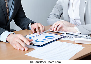 Two business people discuss meeting targets sitting at the...
