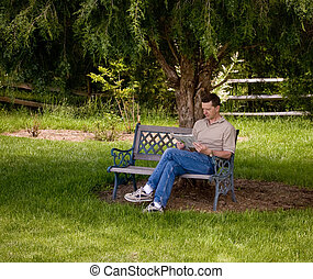 Man reading newspaper under tree - Man sitting on a garden...