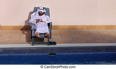 arabian using phone at pool