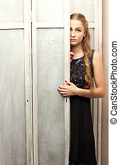girl peeks out from behind the closet door - A girl in a...