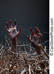 Zombie stretching his creepy hands from the grave, Halloween...