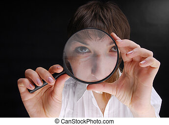 look! - Young woman holding magnifying glass on black...