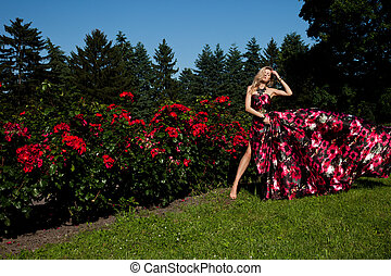 beautiful fashionable woman in a garden with roses