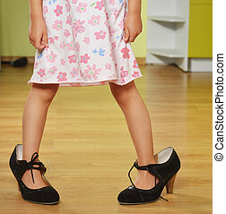 girl in big shoes - Funny little girl in her mothers big...