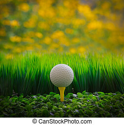 golf ball on green grass field and yellow blur background
