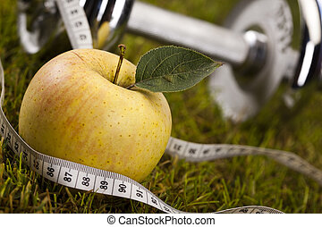 Weight loss, fitness - Apple with measuring of dumbbell