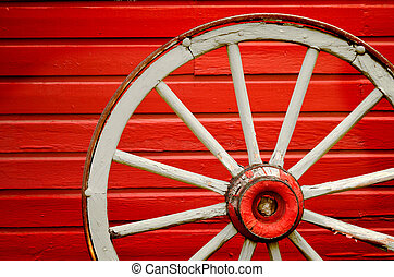 Wagon Wheel by Painted Red Wall - Old weathered wagon wheel...
