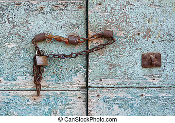 blue gate with peeling paint and rusty chain and padlock