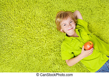 Child lying on the green carpet background, holding apple. Boy smiling and looking at camera
