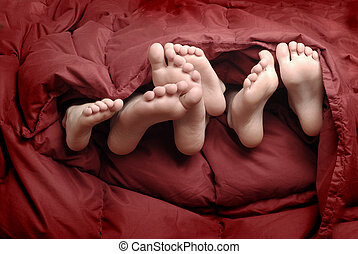 Feet in Bed - Several feet poking out of blankets on bed