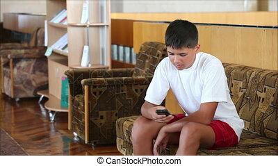 schoolboy plays the game on the Smartphone
