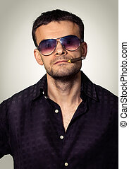 Stern man in sunglasses with a cigar