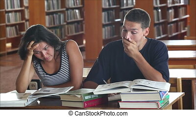 tired students in the library reading books 1