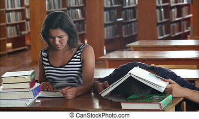 tired students in the library reading books 2