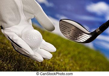Golf ball in hand - Golf ball on green grass over a blue sky...