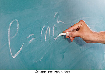 Einsteins Formula E=mc2 on a blackboard - Male hand is...