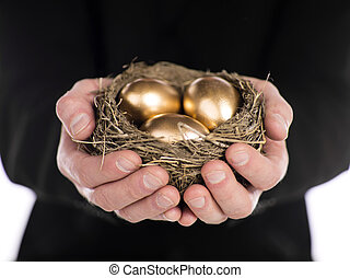 businessman holding nest with gold eggs - Close-up shot of a...
