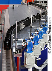 Production line - Automated conveyor belt with bottles at...