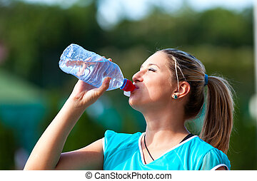 Young sportswoman drinking water from bottle - Closeup of a...