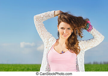 Portrait of joyful charming young woman in a green field