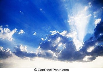 blue cloudy sky and bright sun beams