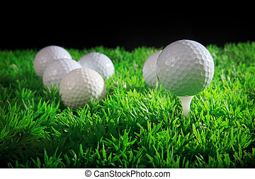 golf ball on tee with green grass and black background