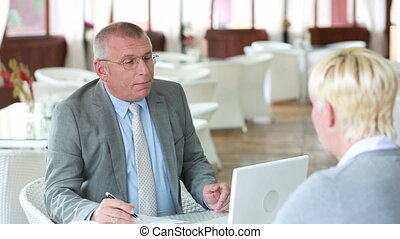 Job interview at cafe - Senior businessman interviewing a...