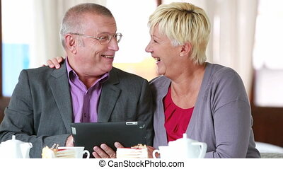 Modern seniors - Senior couple having no trouble using a...
