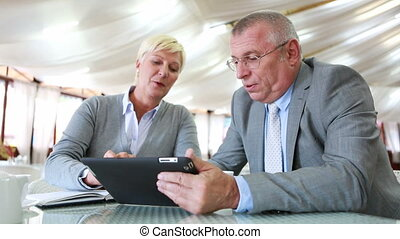 Exchanging ideas - Senior businesspeople sharing ideas at...
