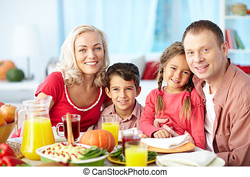 Thanksgiving family - Portrait of happy family sitting at...