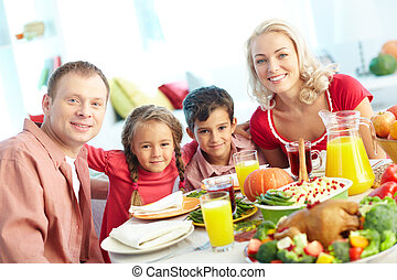 Family by festive table - Portrait of happy family sitting...