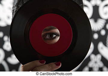 Eye of the record - young woman looking through the hole of...
