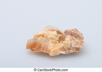 Orange calcite chunks on light background