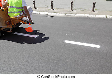 Road marking - Fresh painted lines at road and man putting...