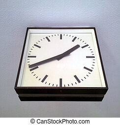 Square station clock hanging on wall
