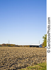 Tilled Field With Farm Building