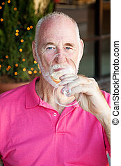 Senior Man Enjoys a Glass of Wine - Senior man enjoying a...