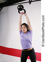 Athletic young woman doing a fitness workout with Kettlebell...