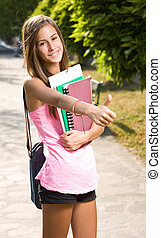 Big thumbs up by beautiful teen student. - Big thumbs up by...