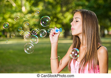 Cute bubble blower. - Portrait of a beautiful young girl...